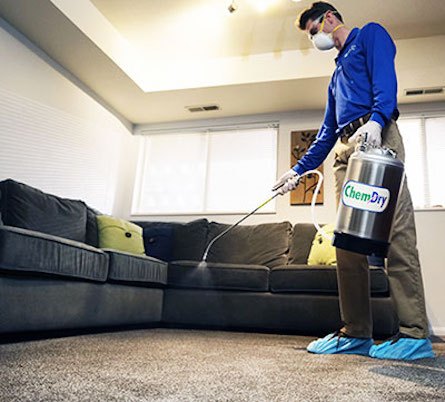 Chem-Dry technician applying hospital-grade sanitizer to carpet and upholstery